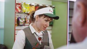 Woman at Cash Carries out Transaction at Petrol Station. KAZAN, TATARSTAN/RUSSIA - AUGUST 25 2017: Closeup pretty polite woman at cash register serves customer stock video footage