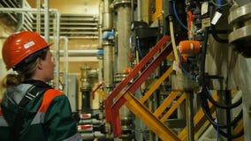 Worker Turns on Mechanism Reports Using Radio Set. KAZAN TATARSTAN/RUSSIA - AUGUST 21 2017: Closeup side view female worker turns on mechanism and reports using stock video footage