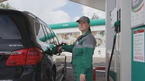 Petrol Station Worker Fills Tank with Refueling Gun. KAZAN, TATARSTAN/RUSSIA - AUGUST 22 2017: Side view petroleum station female worker in uniform serves client stock video footage