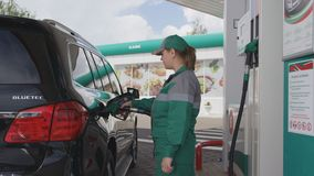 Employee Fills Automobile Tank with Refueling Gun Side View. KAZAN, TATARSTAN/RUSSIA - AUGUST 22 2017: Side view skilled employee in uniform serves client stock footage