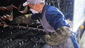Worker in respirator connects wires to accumulators for test stock video footage