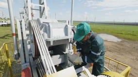 Skilled Worker Turns Round Lever on Modern Pump Jack. KAZAN, TATARSTAN/RUSSIA - AUGUST 23 2017: Skilled worker in Tatneft uniform turns round lever and touches stock video footage