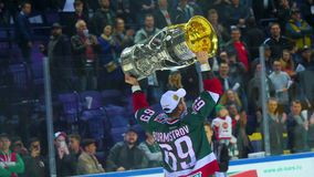 Player of champion team shows trophy cup to cheerful fans