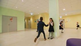 Happy schoolchildren play tag running along hall at break