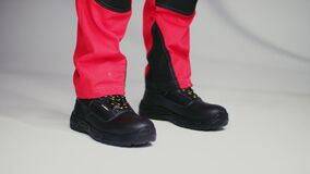 Laborer in modern uniform and work boots on white closeup