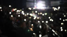 People hold phones with flashlights on spectator places