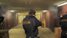 Security men train gun shooting in rifle range. KAZAN, TATARSTAN RUSSIA - MAY 014 2018: Backside view security men in dark uniform train gun shooting skill in stock video