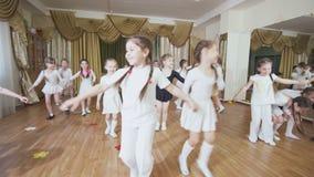Little girls train funny dance for performance in studio. KAZAN, TATARSTAN RUSSIA - MAY 03 2018: Cute joyful little girls train funny dance for performance in stock footage
