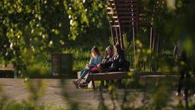 Happy teenage girls talk sitting on wooden bench in garden