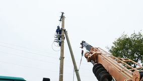 Worker connects electrical wires to line on pole stock footage