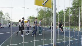 Young people play basketball on sports ground among park stock video footage