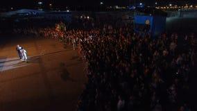 Drone Flies above Crowd and Showmen Speak at Dark Night. KAZAN, TATARSTAN/RUSSIA - NOVEMBER 07 2017: Drone flies above large music fan crowd at festival stage stock video