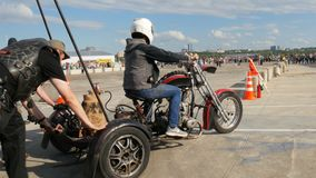 Men Push Motorcycle Helping Biker to Start Motor on Square. KAZAN, TATARSTAN/RUSSIA - NOVEMBER 07 2017: Two strong men push motorcycle helping biker start motor stock video footage