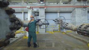 Employee in Green Uniform Turns Lever on Pipelines. KAZAN, TATARSTAN/RUSSIA - SEPTEMBER 19 2017: Backside view employee in green uniform turns round lever on stock video footage