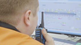 Employee Watches Indicators Reports on Radio Set