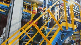 Oil Factory Employee Climbs up Stairs to Equipment