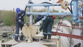 Workers Stand on Cistern Car Lower Pipe into Tank. KAZAN, TATARSTAN/RUSSIA - SEPTEMBER 12 2017: Plant employees stand on cistern and lower equipment pipe into stock footage