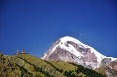 Kazbeg Berg und heilige Dreiheit-Kirche lizenzfreies stockfoto