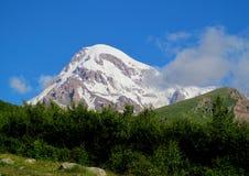 Kazbek berg som täckas med insnöade Caucasian berg i Georgia Arkivfoto