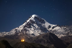 Kazbek at night. Snowcapped peak of mount Kazbek at night under a sky full of stars with Gergeti Trinity church at Georgia Royalty Free Stock Images