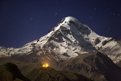 Kazbek at night. Snowcapped peak of mount Kazbek at night under a sky full of stars with Gergeti Trinity church at Georgia Royalty Free Stock Image