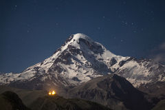 Kazbek at night. Snowcapped peak of mount Kazbek at night under a sky full of stars with Gergeti Trinity church at Georgia Stock Image