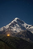 Kazbek at night. Snowcapped peak of mount Kazbek at night under a sky full of stars with Gergeti Trinity church at Georgia Stock Images