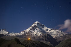 Kazbek at night. Snowcapped peak of mount Kazbek at night under a sky full of stars with Gergeti Trinity church at Georgia Stock Photo
