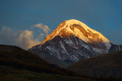 Kazbek at sunrise. Sunlighted top of  snow covered mount against blue sky background. Sunrise scene. Mount Kazbek is one of the major mountains of the Caucasus Royalty Free Stock Photo