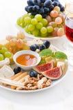 kazen, vruchten, wijn en snacks op plaat, verticale close-up Stock Fotografie