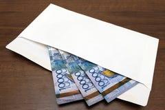 Kazkh在一个白色信封的金钱钞票在桌上说谎 三万坚戈为礼物或贿款准备 作为背景诱饵概念美元灰色吊异常分支 库存图片