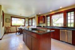 Küche mit Insel und dunklem hölzernem Fußboden. Stockfotografie