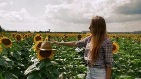 Kciuk w górę szczęśliwej średniorolnej dziewczyny stawia jego kapelusz na słoneczniku zbiory