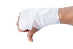 Kciuka puszek pokazuje ręką z biel bandażami odizolowywającymi Obrazy Stock
