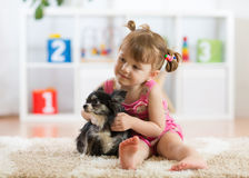 Kd and dog play in a nursery Royalty Free Stock Images