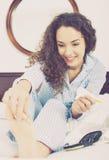 Kędzierzawa dziewczyny nacierania śmietanka w palec u nogi Zdjęcie Stock