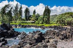 Keanae Peninsula, Maui Hawaii. The water crashes against the black rocks at the Keanae Penisula in Maui, Hawaii Stock Photo