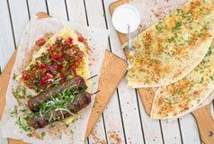 Kebab和Gozleme 剁碎的牛肉或羊羔传统东方肉kebab与菜和草本顶上的大理石切口公猪 免版税库存照片