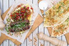 Kebab和Gozleme 剁碎的牛肉或羊羔传统东方肉kebab与菜和草本顶上的大理石切口公猪 库存图片