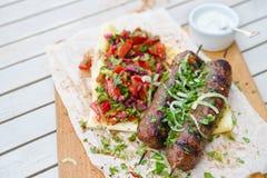 Kebab 剁碎的牛肉或羊羔传统东方肉kebab与菜和草本顶上的大理石切口公猪 免版税库存图片