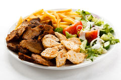 Kebab. Grilled meat, French fries and vegetables royalty free stock photos