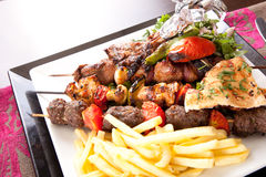 Kebab. Grilled kebab,  onion skewers with fries, salad and crouton Stock Photography