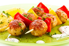 Kebab. Grilled meatballs with fruits and vegetables royalty free stock images