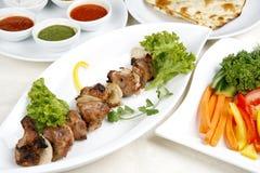 Kebab apetitoso del shish con los tomates y los verdes Imagen de archivo libre de regalías