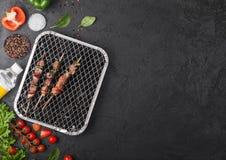 Kebab arrostito della carne di maiale con paprica sulla griglia eliminabile del bbq del carbone con gli ortaggi freschi su blackb immagine stock