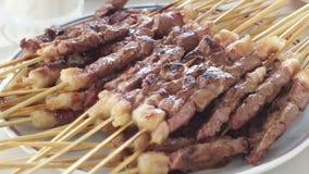Kebab asado caliente de la carne con el pincho en la placa Clientes que toman kebabs con las manos en el restaurante almacen de video