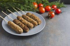 Kebab asado a la parrilla del lule en la placa gris, tomates frescos, manojo de eneldo en la tabla de cocina oscura Espacio libre imágenes de archivo libres de regalías