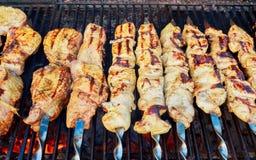 Kebab asado a la parrilla en el pincho del metal El cocinero da cocinar la barbacoa asada de la carne con las porciones de humo Foto de archivo