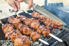 Kebab asado a la parrilla que fríe en los pinchos del metal Carne asada cocinada en la barbacoa con humo Cierre para arriba imagenes de archivo