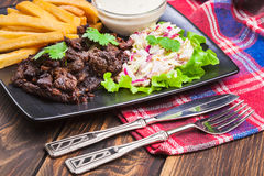 Kebab of beef with french fries and salad Stock Images
